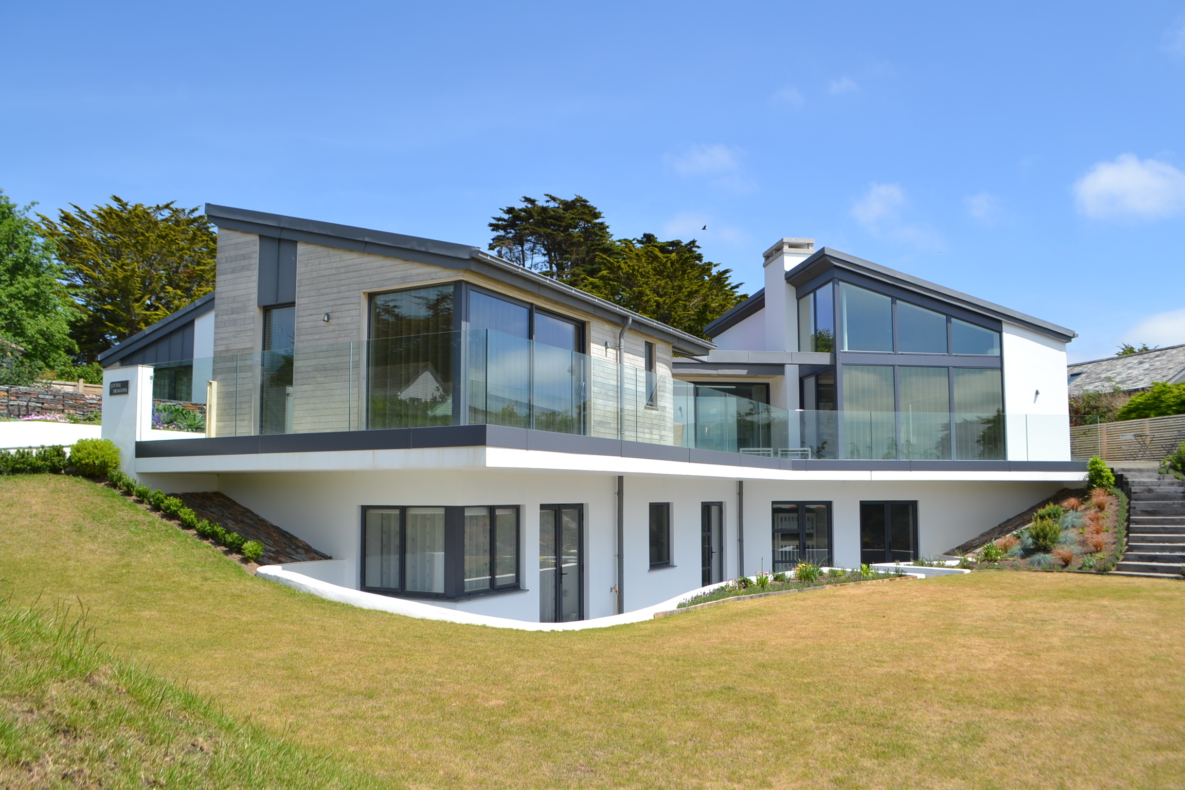 House exterior, cantilevered deck, landscaped garden, floor to ceiling glazing in steel frame first floor.