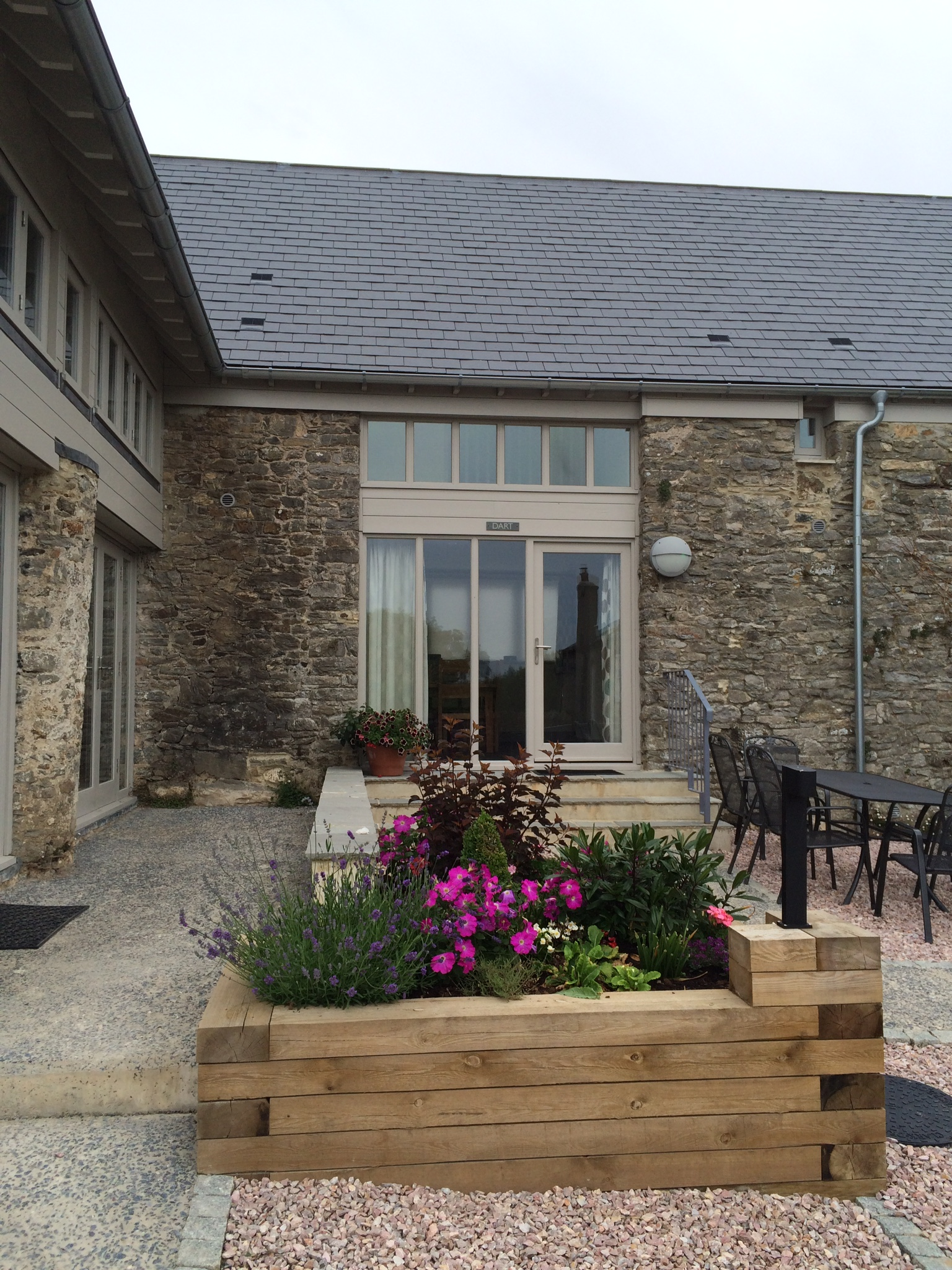 Barn conversion, new slate roof, repointed walls, timber planter with flowers in foreground.